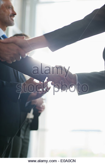 Close up of business people shaking hands in a row - Stock Image
