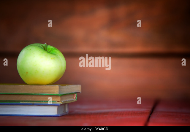 Apple on pile of books. Education concept, back to school. - Stock Image