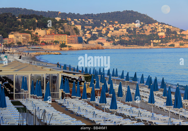 Beach along Promenade Des Anglais street in Nice, France on the French Riviera, as the full moon is rising and the - Stock Image
