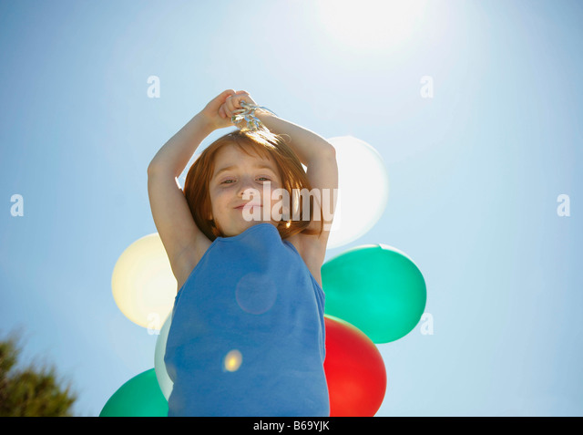Young girl holding balloons overhead - Stock Image
