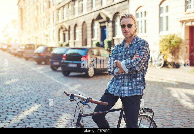 Portrait of man on his bike with arms crossed looking stylish. City lifestyle - Stock-Bilder