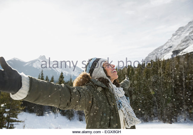 Exuberant woman with arms outstretched below snowy mountain - Stock Image