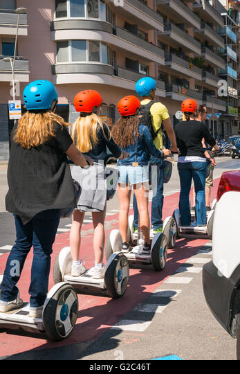 Spain Catalonia Barcelona Eixample group of young teenage girls on Segway type electric scooters with crash helmets - Stock Image