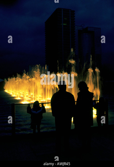 People silhouetted in front of fountain at night - Stock Image