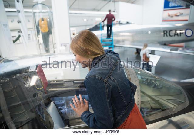 Curious girl looking inside airplane cockpit in war museum hangar - Stock-Bilder