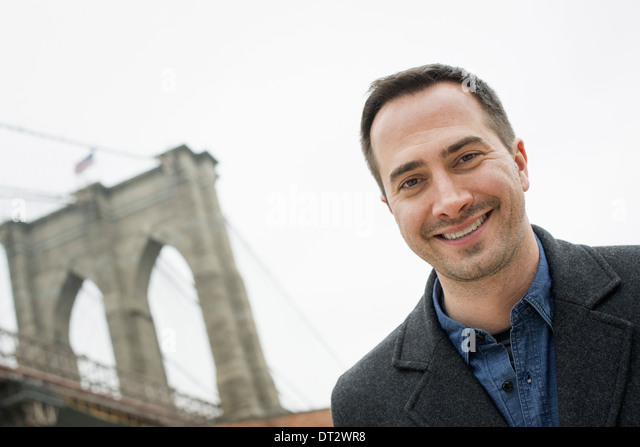 New York city the Brooklyn Bridge crossing over the East River A man looking at the camera and smiling - Stock Image