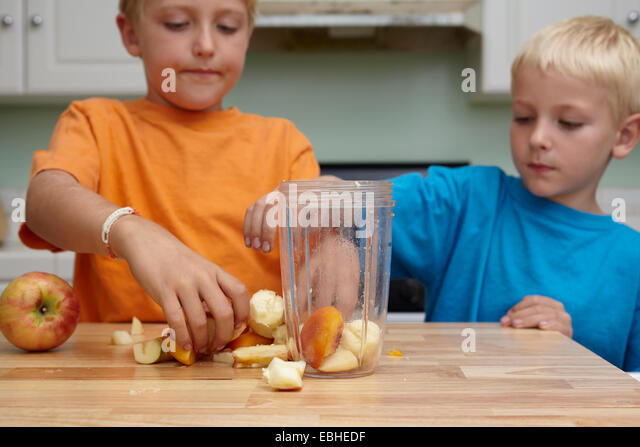 Brothers blending fruits in kitchen - Stock Image