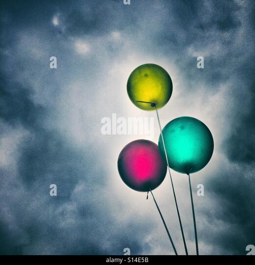 Three balloons against a dark cloudy sky - Stock Image