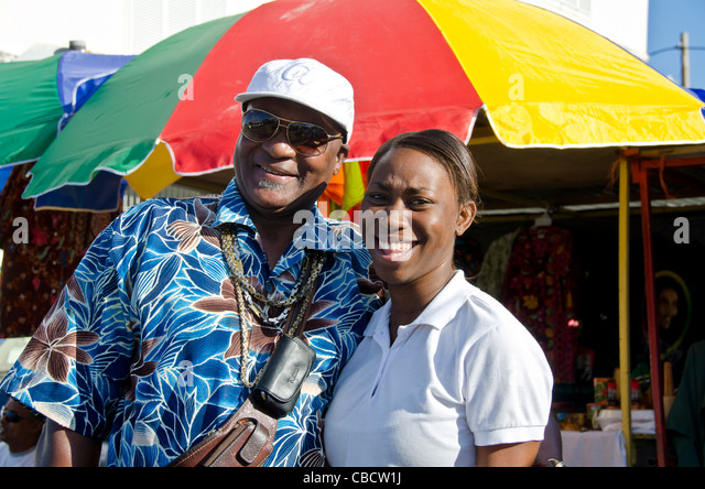 Taxi driver with daughter smiling next to bright umbrella, Roseau Dominica - Stock Image