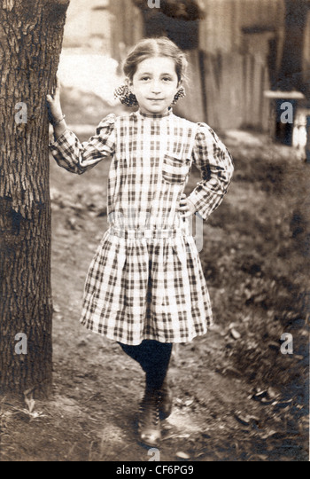 Vintage photo of young girl outdoors standing by a tree wearing a plaid dress, circa 1910. - Stock Image