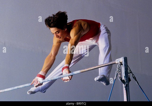 Male gymnast performing on the horizontal bar. - Stock Image
