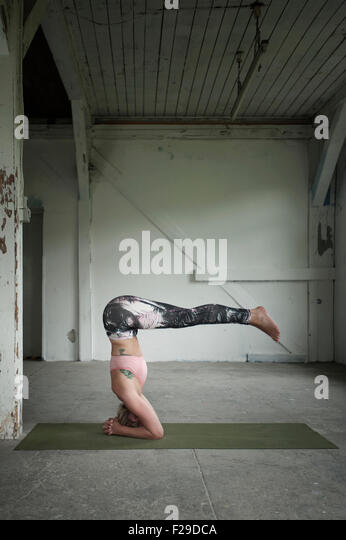 Mid adult woman practicing headstand pose in yoga studio, Munich, Bavaria, Germany - Stock Image