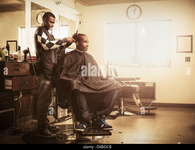 Barber in traditional barber shop shaving man's head - Stock-Bilder