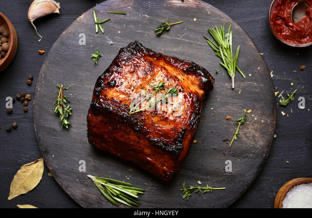 Roasted pork on wooden board, top view, close up - Stock Image