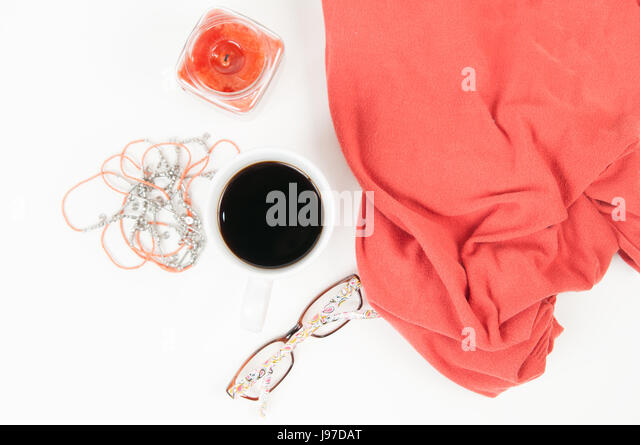 Feminine Flat Lay of coffee, candle, glasses, blanket and necklace on a white background - Stock Image