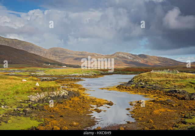 Sunny tranquil view craggy landscape and stream, Loch Aineort, South Uist, Outer Hebrides - Stock Image