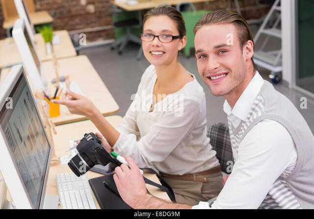 Smiling photo editors using computer in office - Stock Image