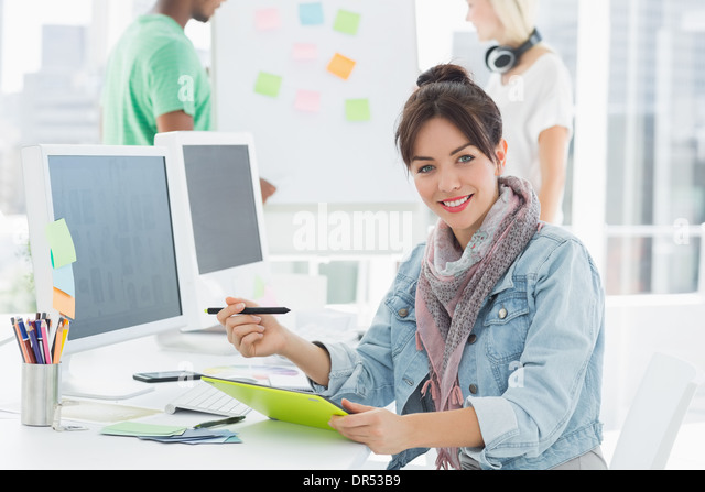 Artist drawing something on graphic tablet with colleagues behind - Stock Image