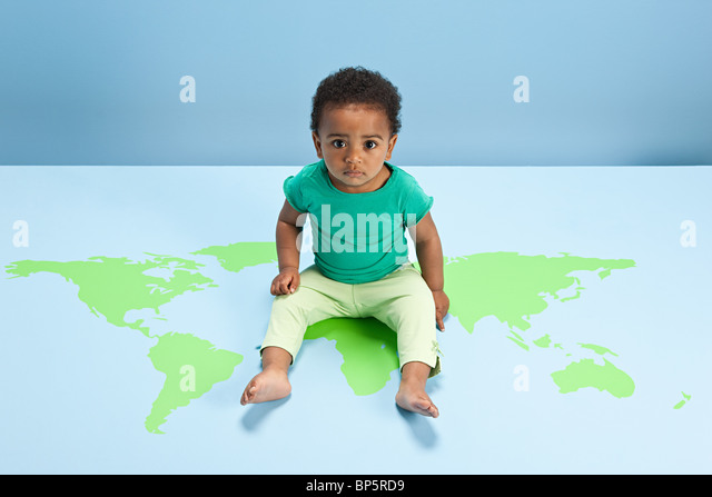 Baby boy sitting on world map on floor - Stock Image