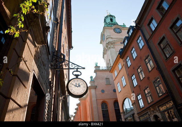 Clock outside shop & The clocktower of Storkyrkan (The Great Church), Gamla Stan, Stockholm, Sweden - Stock Image