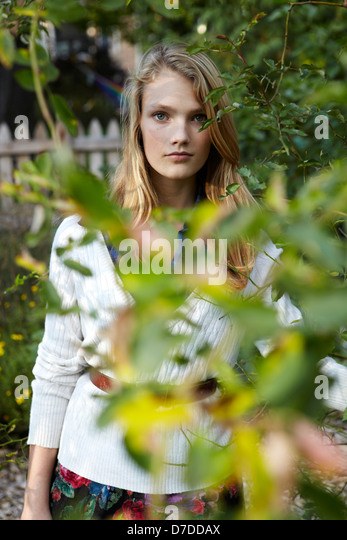 Beautiful teen behind tree in garden - Stock Image