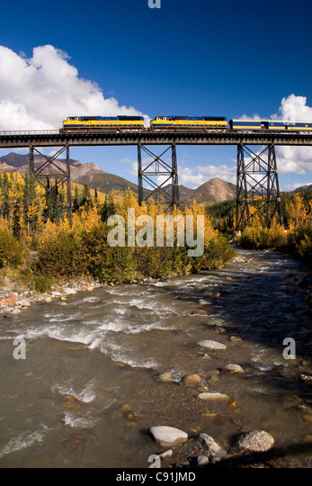 Riley Creek flows under the trestle as a northbound Alaska Railroad passenger train crosses a trestle, Southcentral - Stock Image