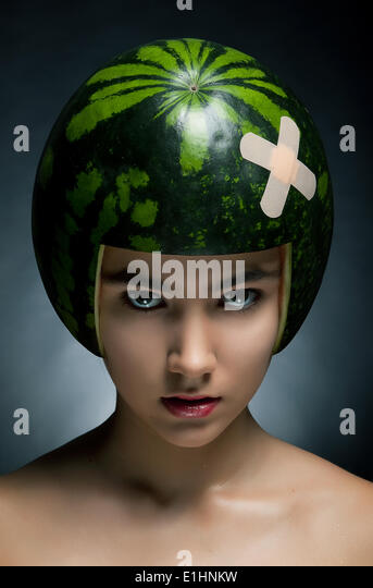 Young hair fashion model with ripe fresh watermelon as a helmet - Stock Image