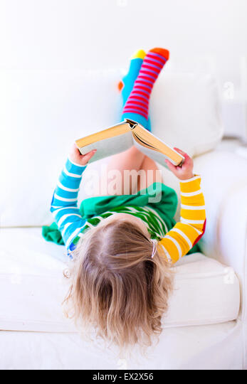 Little girl reading a book relaxing on a white couch. Kids read books at home or preschool. Children learning and - Stock Image