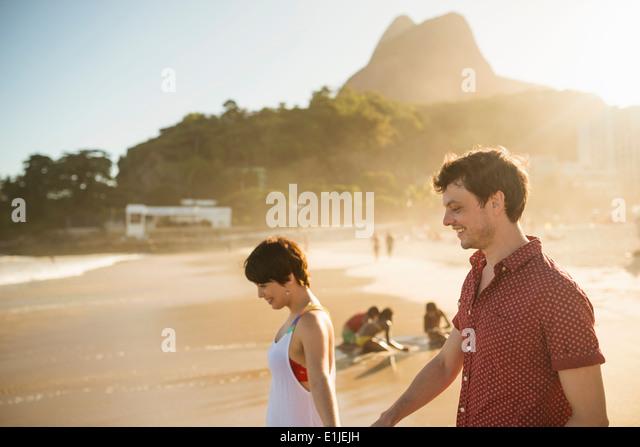 Young couple enjoying sunset, Ipanema Beach, Rio, Brazil - Stock Image