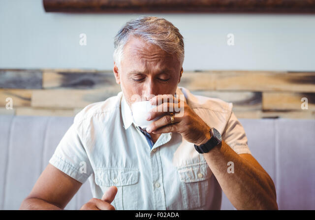 Casual man enjoying a cup of coffee - Stock Image