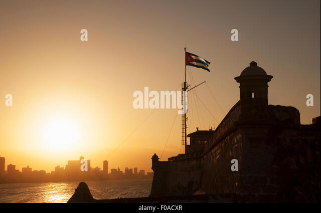 Cuban flag over El Morro Fortress at sunset, Havana, Cuba - Stock Image