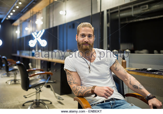 Portrait of confident hipster hairstylist in hair salon - Stock-Bilder