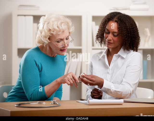 Doctor and patient looking at medicine - Stock Image