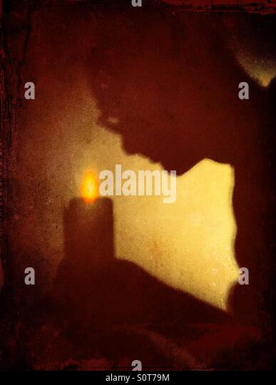 Shadow of man bent over candle - Stock-Bilder