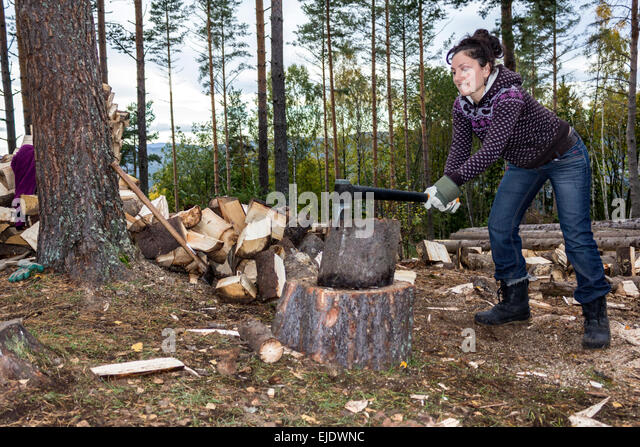 Young woman chopping wood in a forest no sales on alamy or anywhere