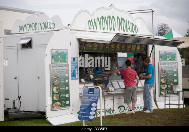 people buying Indian food from takeaway truck with welsh signage at National Eisteddfod of Wales Cardiff August - Stock Image