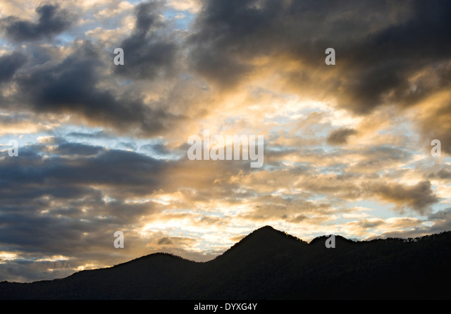 Silhoutted mountain range & sunset sky, QLD Australia - Stock Image