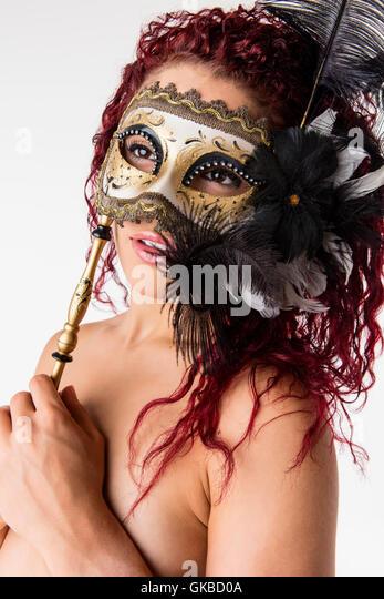 Young redhead with a masquerade mask in studio, Virginia Beach, VA - Stock Image