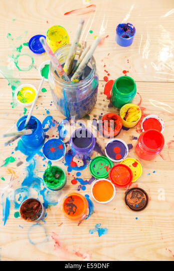 Jars of paint and paintbrushes on wooden table - Stock Image