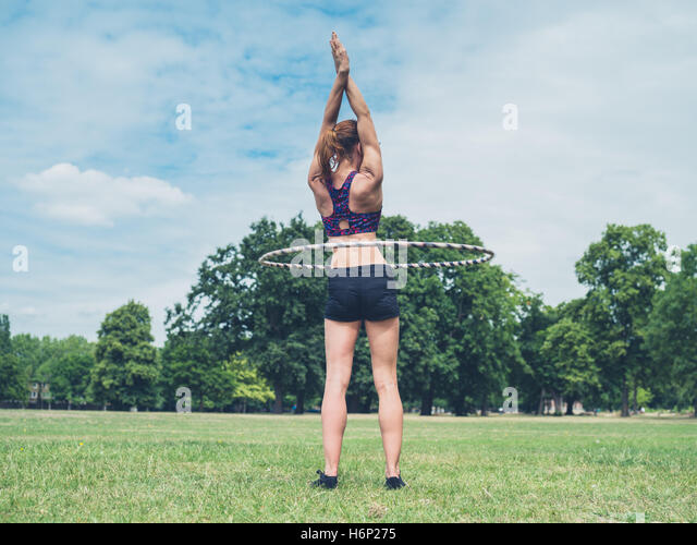 A fit and athletic young woman is working out with a hula hoop in the park on a sunny summer day - Stock Image