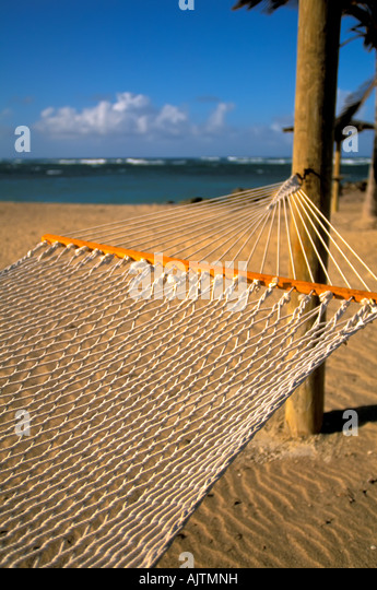 white rope hammock on tropical beach, Island of Nevis, St Kitts and Nevis Caribbean island,   Pinney's Beach, - Stock Image