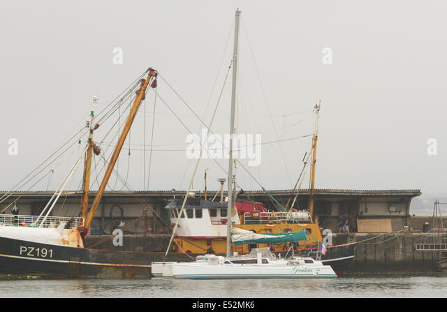 Newlyn, UK. 18th July, 2014. The Penlee RNLI Lifeboat tows a 30 foot Trimaran into Newlyn Harbour after stormy weather - Stock Image