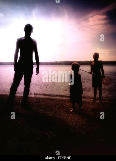 Silhouette Man And Children Standing Against Lake During Sunset - Stock Image