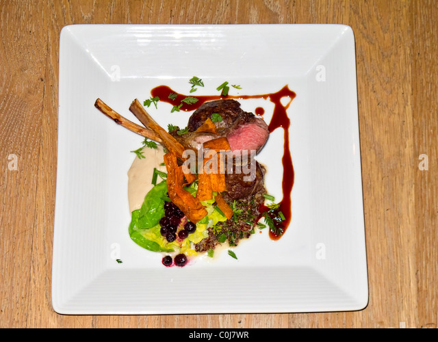 Entree, rack of lamb, served with house made lamb sausage, quinoa and a cauliflour puree at Talisker On Main, restaurant. - Stock Image