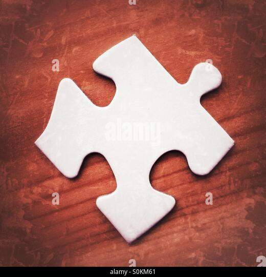 Blank white jigsaw puzzle piece on a wooden surface with grunge filter effects - Stock Image