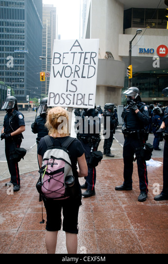 A protester holding up a sign in front of riot police during the G20 Summit in Toronto in the summer of 2010. - Stock Image