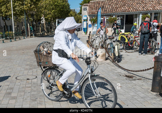 Lady on bicycle in La flotte, Ile de Re, Nouvelle-Aquitaine, french westcoast, france, - Stock Image