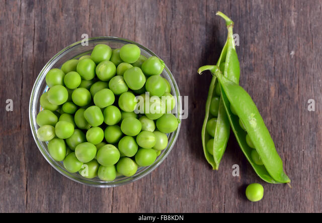 Close up of fresh peas on wooden table - Stock Image