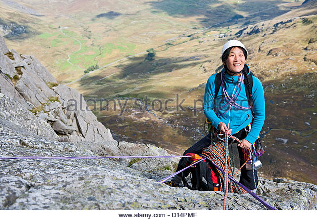 Female rock climber at an anchor point and belaying - Stock Image