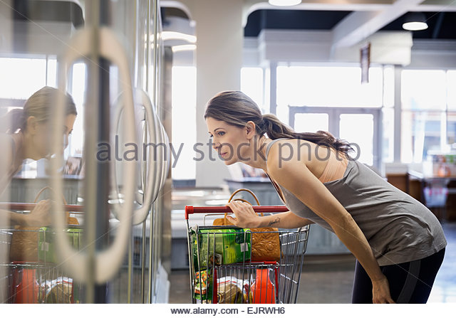 Woman shopping frozen foods in grocery store - Stock Image